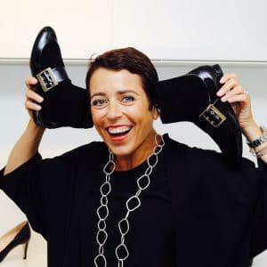 Schuhe an Ohr haltende Frau